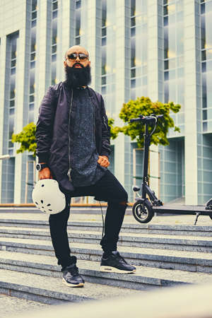 Stylish bearded male on a step over electric scooter background.