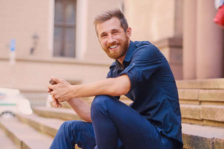 Stylish bearded positive male in a jeans and denim jacket sits on a step and using a smartphone.