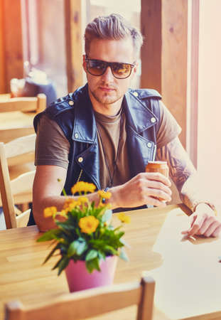 Attractive young blond bearded male dressed in a leather jacket sits at the table and drinks juice. Reklamní fotografie