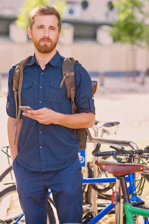 Portrait of bearded hipster male using smartphone outdoor. Reklamní fotografie