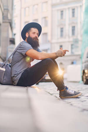 The full body image of casual bearded hipster sits on a step on a street.