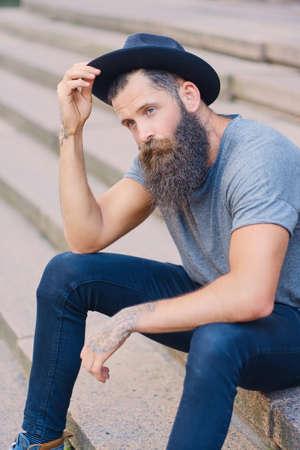 Portrét vousatého muže v klobouku s tetováním na pažích, sedí na schodech.