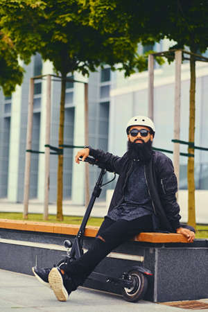 Stylish bearded male in sunglasses relaxing on a bench after riding by electric scooter in downtown.