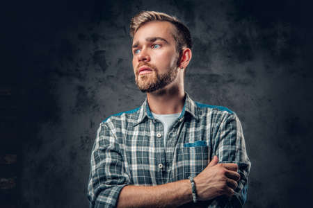 Studio portrait of a blue eyed, bearded hipster male with crossed arms over grey background.