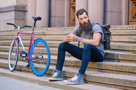 Bearded tattooed hipster sits on a step and using a smartphone with single speed bicycle on background.
