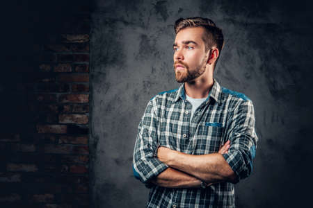 hairdresser: Studio portrait of a blue eyed, bearded hipster male with crossed arms over grey background.
