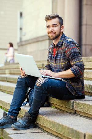 Neformální vousatý muž oblečený v džínách a fleece košili sedí na schodech a pomocí přenosného počítače. Reklamní fotografie