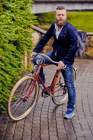Redhead bearded male dressed in a blue jacket and jeans on a retro bicycle in a park.