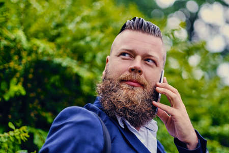Portrait of bearded hipster male using smartphone outdoor. Stock Photo
