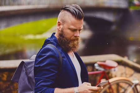 Bearded hipster male using smartphone in a park near river. Reklamní fotografie