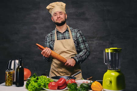 Funny male chef cook posing near the table with a lot of fresh vegetables. photo