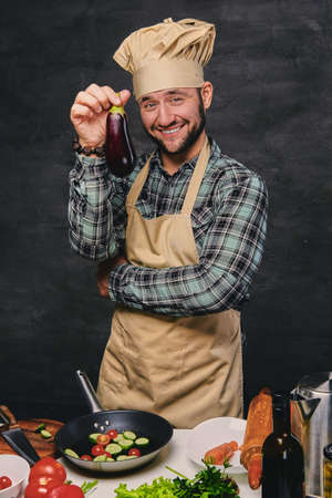Portrait of bearded chef cook holds eggplant. photo
