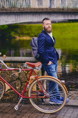 hairdresser: Redhead bearded male dressed in a blue jacket and jeans on a retro bicycle in a park.