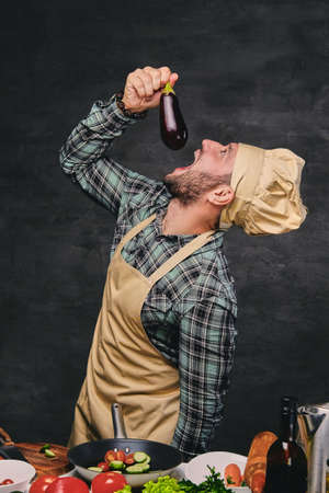 Funny bearded chef cook eats eggplant. photo