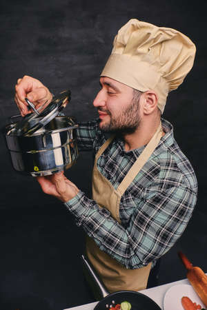 Funny bearded chef cook tasting the soup from a pan. photo
