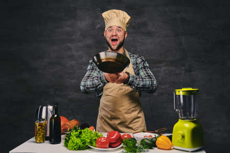 Studio image of male chef cook preparing meals on a pan. photo