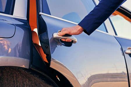男のイメージに近い車のドアが開きます。 写真素材