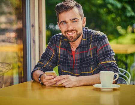 Bearded male dressed in a fleece shirt, drinks coffee in a cafe.