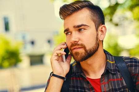 Bearded male dressed in a fleece shirt talks by a smart phone in a park. Close up. Stock Photo