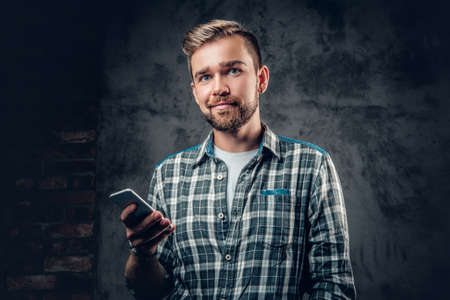 Bearded hipster male in a fleece shirt holds smart phone over grey background.