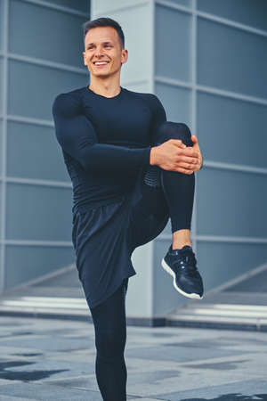 Sporty athletic male is warming up and stretching outdoors over modern building background.