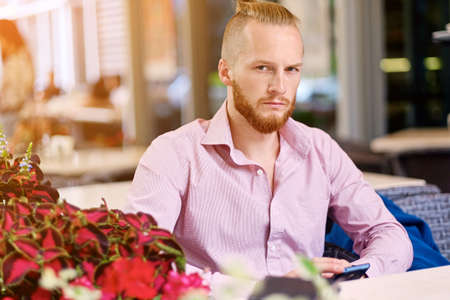 Portrait of bearded redhead male in a pink shirtt at the table in a cafe.