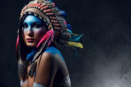 インディアンの羽の帽子とカラフルなメイクアップでシャーマンの女性の肖像画を閉じます。