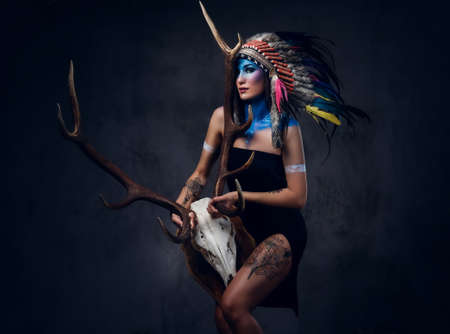 Shamanic female with Indian feather hat and colorful makeup holds an antler skull over grey background. Stock Photo