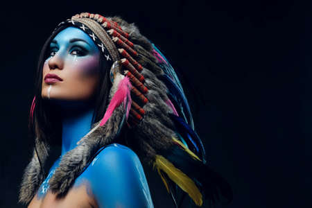 Close up portrait of shamanic female with Indian feather hat and colorful makeup.