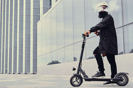 Bearded hipster male vaping and riding by electric scooter over modern building. Stock Photo - 86532558