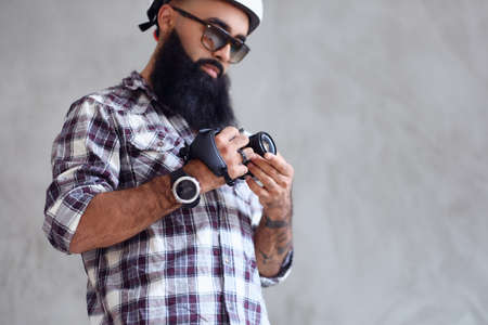 A bearded hipster amateur photographer with tattoos on arms, dressed in a fleece shirt holds compact DSLR camera over grey background. Reklamní fotografie