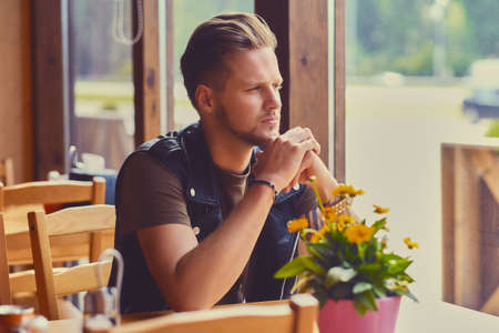 Attractive young blond bearded male dressed in a leather jacket sits at the table in a cafe. Reklamní fotografie