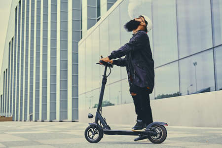 Bearded hipster male vaping and riding by electric scooter over modern building. 免版税图像
