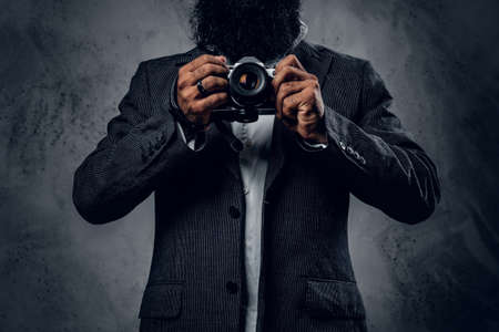 Elegant bearded professional photographer in a suit shooting with a compact DSLR camera.