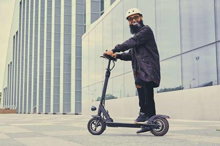 流行に敏感なひげを生やした男性 vaping とモダンな建物の電気スクーターで乗馬。