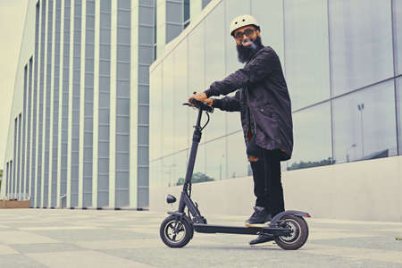 Bearded hipster male vaping and riding by electric scooter over modern building. Foto de archivo