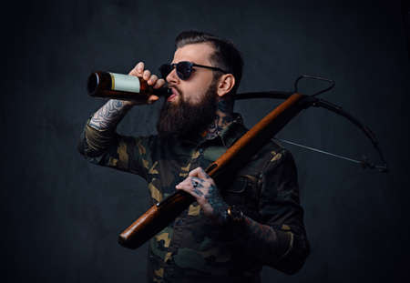 A brutal tattooed, bearded male dressed in a military jacket holds the craft beer bottle and a crossbow.