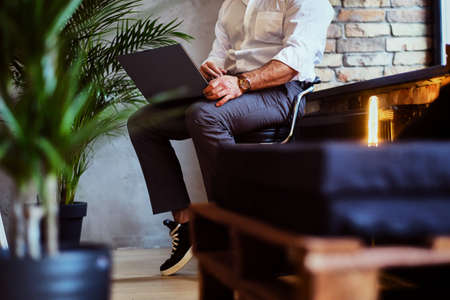 Stylish bearded male works with a laptop in a room with loft interior.