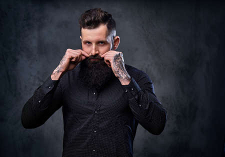 Stylish bearded male in a black shirt with tattoos on his arms.