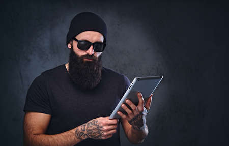 Bearded brutal male in a hat and sunglasses holds tablet PC over grey background. Reklamní fotografie