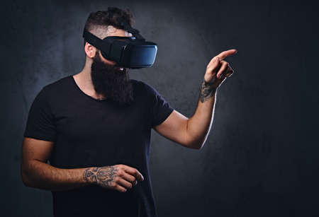 Bearded male with tattoos on arms wearing VR glasses.