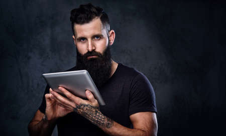 Bearded male with tattooed arms holds silver tablet PC over grey background. Stock Photo
