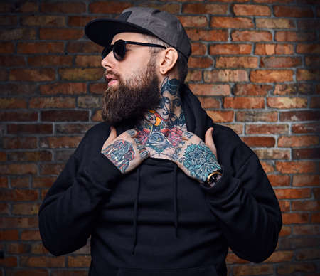 Modern bearded hipster male with tattoos on his arms, dressed in a military jacket posing over vintage wall from a red brick. Reklamní fotografie - 88490037