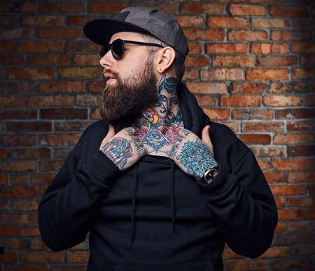 Moderno uomo barbuto hipster con tatuaggi sulle braccia, vestito con una giacca militare in posa sul muro vintage da un mattone rosso. Archivio Fotografico