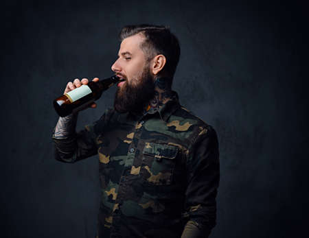 A tattooed, bearded hipster male dressed in military shirt, drinks craft beer from a bottle. Reklamní fotografie