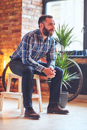A bearded hipster male dressed in a fleece shirt sits on a wooden chair, near the window in a room with loft interior Stock Photo