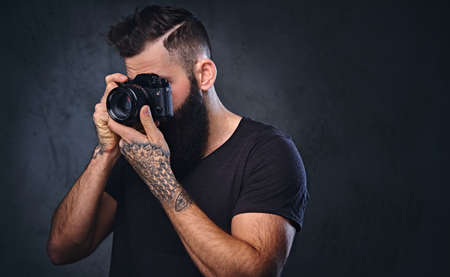 The brutal tattooed, bearded male taking picture with a professional camera. Reklamní fotografie