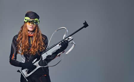 carrera de relevos: Studio portrait of a redhead female Biatlon champion holds a gun over grey background.