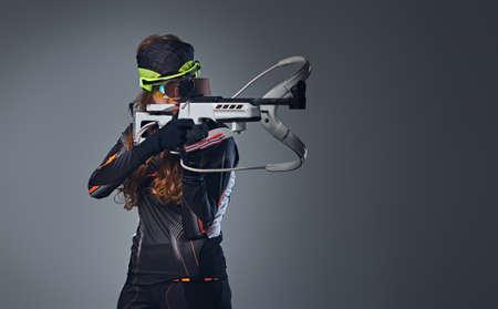 carrera de relevos: Redhead female Biathlon champion aiming with a competitive gun in a studio over grey background.