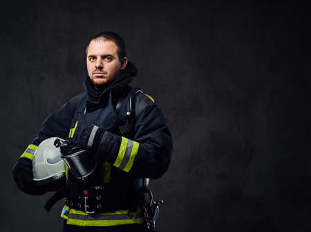 Studio portrait of firefighter dressed in uniform holds safety helmet in his arm.